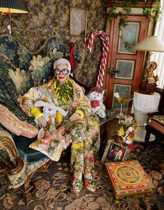 Vivienne Westwood polyester/silk trenchcoat, £2,645, silk Brighella dress, £2,075, and Vivienne Westwood x Grenson canvas and leather shoes, £350. Wolford nylon tights, £25. Pebble London painted wood parrots and leaves necklace, £165, resin and plastic bananas necklace, £145, wooden bead necklace, £120, brass chain with painted corn on the cob pendant, £145, and wire and glass bead cuff, £90 (right arm top). Michelle Lowe-Holder flocked bangle (right arm bottom), £125, tulle Donut cuff…
