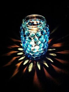 Mason jar with glass marbles glued on the outside and a tea light or LED light inside.