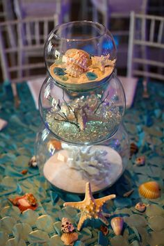 As attendees walk down the stairs they submerge under the sea.  Two glass boxes with coral reef deco inside create an entryway for guest and opens up the dining area and dance floor.  Ruffled aqua blue liens cover the circle table.  Long rectangle glass tables are compete with coral decor in the bottom and glow …