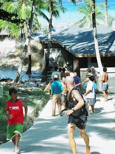 """This photo, taken Dec. 26, 2004, shows people fleeing as a tsunami wave comes crashing ashore at Koh Raya, part of Thailand's territory in the Andaman islands. The photographer who took this picture escaped without injury, but retreated at the first wave and watched as a second wave tore apart the wooden buildings, with a third and largest wave coming forward and """"ripping apart the cement buildings like they were made of balsa wood."""""""