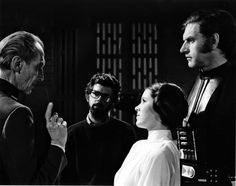EPIC MOMENT! Peter Cushing (Grand Moff Tarkin),  Director George Lucas, Carrie Fisher (Princess Leia), and David Prowse (Darth Vader).  Only one who appears to be in character is Peter Cushing...