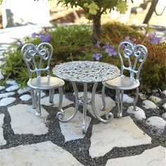 This wee faux aluminum patio set adds modern elegance to the miniature garden.