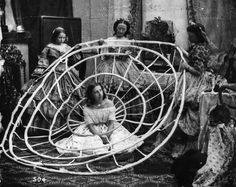 A woman in a London dress shop waits for her crinoline hoops to be finished.