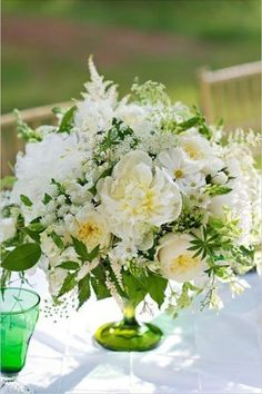 white centerpiece with peonies, garden roses, and daisies in a green glass vase