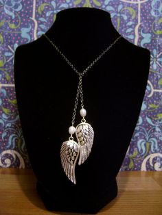Detailed wings hang from a freshwater pearl on either end of this gun metal chain. There is no clasp. The necklace is worn by looping the chain over itself to form a tie.  SOLD