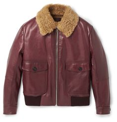 <a href='http://www.mrporter.com/mens/Designers/Prada'>Prada</a>'s latest collection is inspired by a nostalgic and melancholic vision of history. Reminiscent of bombers worn by the fighter pilots of World War II, this burgundy leather flight jacket is trimmed and lined in plush shearling. Made in Italy to the brand's exacting standards, it has plenty of pockets, adjustable cuffs and flexible ribbed wool trims that seal in warmth.