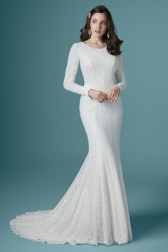 Constructed allover with boho geometric lace, this gown is complete with modest long sleeves, a slight scoop neckline and fabric covered button detail along the back.
