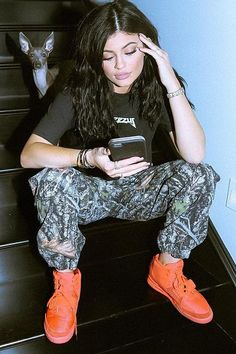 Kylie Jenner wearing Nike Air Red October Yeezy 2 Sneakers, Supreme Cargo Pants in Tree Camo and Nike Air Max 90 Yeezy 2 Red October Sneakers