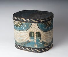 SMALL WALLPAPER COVERED HAT BOX IN A DRAPERY SWAG PATTERN ON A BLUE FIELD WITH FLORAL DECORATION.