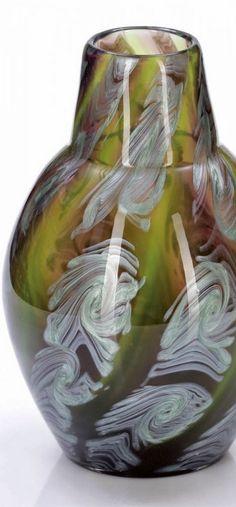 Johann Loetz Wwe., Klostermühle 1911. Dekor: Franz Hofstötter zugeschrieben In farbloses Glas eingeschmolzener Dekor aus grünlichen und violetten Streifen, mit Silberglas übersponnen, die Bänder in sechsteiligem Rippenmodel getrennt und zu Wirbeln verzogen. Modelgeblasen. Ausgeschliffener Abriss. H. 21 cm, D. 13,5 cm.