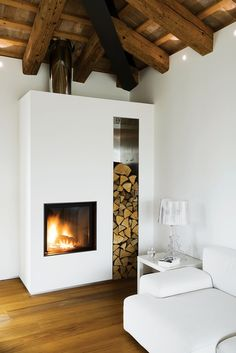 "A rectangular fireplace rests inside a long, vertical white box complete with a wood log storage area. See the rest of this renovated farmhouse in northern Italy story, ""Going Big, Going Home."""