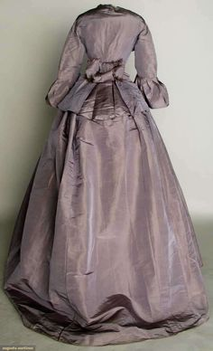 "LILAC SILK DAY DRESS, EARLY 1860s (looks like late 60s to me...)  2 piece faille, peplum bodice, trained skirt, B 36"", W 21.5"", L 41""-57"", (light skirt stains, water stains on peplum, alterations, sleeve flounce basted on) very good."