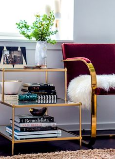 Raspberry chairs with gold arms and sheepskin seat with gold and glass coffee table