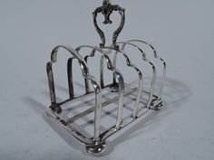 Only one in stock of this item shown.  Edwardian English Sterling Silver Toast Rack Edwardian sterling silver toast rack. Made by Atkin Brothers in Sheffield in 1903. Five trefoil arches mounted to rectangular frame with stretcher on 4 bun supports. Handle comprises 2 joined scrolls. A practical addition to the breakfast tray. Hallmarked. Nice condition and patina. #SterlingSilverToastRack #EdwardianSterlingSilver #WeddingGiftIdea #EdwardianEnglishSterlingSilver