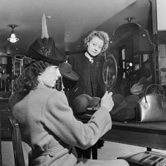 A customer tries on a new hat in the millinery department of Bourne and Hollingsworth on Oxford Street in 1942.