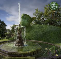 The Topiary Cat takes a drink from a fountain