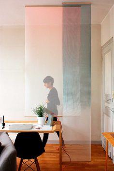 Detalhes da decoração com divisória de tecido. No escritório, home office, o tecido branco faz a divisão do ambiente com escrivaninha de madeira com luminária de mesa branca, cadeira preta, sofá cinza.    #decoracao #decor #details #casadevalentina