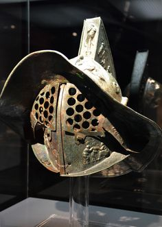 -  Gladiator helmet found in Pompeii and richly decorated with scenes of Greek mythology, Gladiators – Death and Triumph at the Colosseum exhibition, Museum und Park Kalkriese ./tcc/