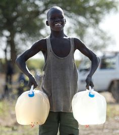 A boy demonstrates the difference between the clean water Oxfam is now providing and the dirty water from the river Nile in Awerial settleme... via Oxfam East Africa