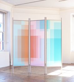 Layer Screens by Kim Thome are room dividers made of two layers of glass with diffusion lighting gels sandwiched between them