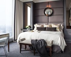 Powell and Bonnell Design Inc. Elegantly designed bedroom in a city apartment. Warm, simple and inviting. Love the padded wall/headboard and the genius placement of a mirror above the bed.