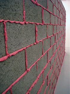 Cinder block wall with hot pink colored grout