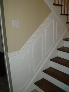 staircase moulding trim on wall. white runners, stained steps.