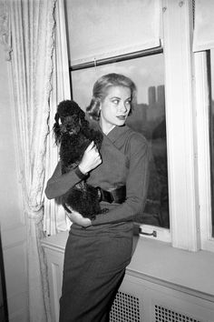 Grace Kelly photographed in her New York apartment with her pet poodle, Oliver, before departing to Monaco for her wedding
