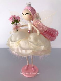 MADE TO ORDER. Pretty little flower fairy doll called Angel, Miniature ooak Fairy/ guardian Angel ornament. She wears an ivory rose petal dress with a pink feather underskirt. She has pink hair and wears a little crown on her head. Angel holds a little bunch of pink roses and has delicate leaf wings. Her face has been hand painted. She comes mounted on a little stand. Approximately 13.5cm tall. Angel would make a beautiful Fairy doll ornament or a Birthday cake topper. The last photograp...