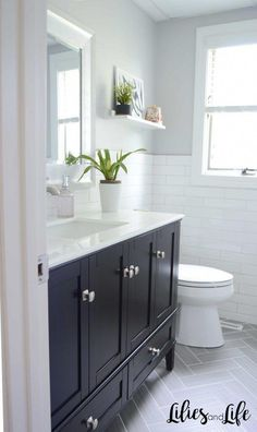 Bathroom remodel idea that includes a complete remodel with gray herringbone floor, white subway tile walls and a black vanity! A modern, bright design with some pops of color! #bathroomremodel #remodel #whitebathroom #moderbathroom #herringbonetile #graytile #simplebathroom #bathroomideas Modern White Bathroom, White Bathroom Tiles, Bathroom Floor Tiles, Simple Bathroom, Black Vanity Bathroom, Master Bathroom, Bathroom Cabinets, Black Bathrooms, Minimalist Bathroom