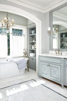 Lovely bath featuring custom cabinetry in a dove grey and basket weave tile and marble floor.