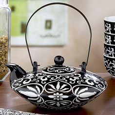 Black/White Hand painted Teapot | World Market  Our stunning hand painted teapot in a dramatic black and white pattern. Inspired by the beauty of traditional Asian floral patterns, our teapot gets a surprising update in a modern ebony and white cutout design. As a display in your dining room or as the centerpiece of your tea service, this is a teapot that delivers striking elegance, sip after sip.  Hand painted porcelain  Matching teacups sold separately  $16.99