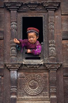 Little Tamang girl in the window of her traditional home, NEPAL