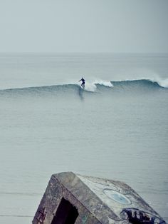 """surfsouthafrica: """" Thomas Lodin is one of the best up-an-coming surf photographers. Here he captures a lone surfer hanging five in Brittany, France. """""""
