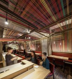 Local studio El Equipo Creativo reinterpreted traditional wooden Peruvian cloth-weaving equipment to create angled panels from thick threads stretched across wooden frames. Some of the frames are twined with white cords to contrast with the colourful sections.