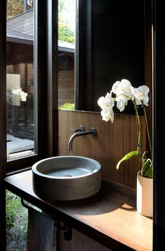 In this small powder room, there's a window with views of the courtyard from the vanity. #SmallBathroom #PowderRoom #Bathroom #Window