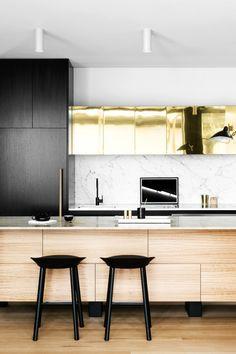 Black and gold kitchen with marble backsplash
