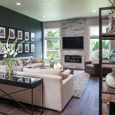 The dark accent wall, fireplace and custom wood floors add warmth to this open, modern living room. Big windows flood the space with tons of natural light.