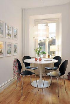 mesa branca e cadeiras pretas.