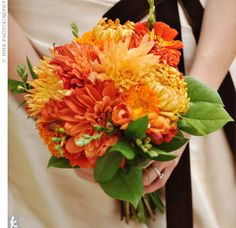 bouquet of orange dahlias, mums, ranunculus, anemones, and green ...