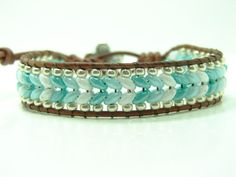 This beautiful ombre single wrap bracelet is made of 2.5 x 5mm green, light green, white Superduo beads that have been woven into the Herringbone stitch surrounded by silver seed beads. Using the Spanish knot on both ends of the brown distressed leather cord and a silver metal button for the closure. The bracelet has two sizes that measures at approximately 7 1/4 & 8 1/4 from the loop to the button. If you need a different size, let me know at check out. It will add 1-3 days to ...