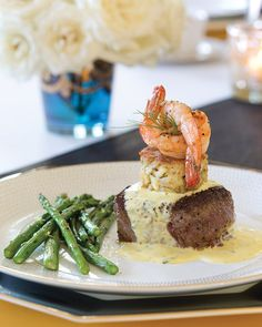 This exquisite Steak Oscar entree is a rich slice of steak crowned with dill-flecked crab cakes and roasted shrimp.