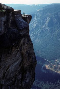 Can you see the tiny hiker standing on a jutting point on a massive cliff at Taft Point in Yosemite National Park?