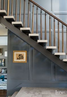 Contemporary Entry Staircase. Lacquered paneling complements the entry's bronze-plated-and-stone staircase. Photography: Karyn Millet