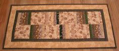 """This handmade quilted table runner is made from cotton fabrics in browns, beiges, and some greens pieced together in blocks and strips. Size is 15-3/4"""" x 34"""" (31-40-5)"""