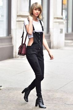 Black Long Ripped Dungaree Paired With White Crop Top, Black Boots And Maroon Bag.