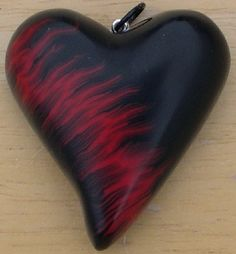 Simple black polymer clay heart with red flames. BigKERM
