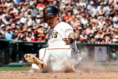 SLIDING HOME:    Joe Panik (12) of the San Francisco Giants slides into home plate to score a run against the San Diego Padres during the fifth inning at AT&T Park on April 30, in San Francisco, Calif.