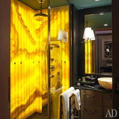 Стенки душевой кабины сделаны изоникса. Мебель для ванной сбронзовыми ручками имраморной столешницей, Promemoria.
