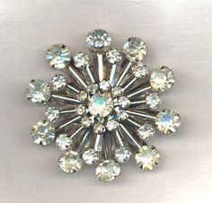 """During the 1950's some jewelry had an """"atomic"""" motif. Those of you old who are old enough might remember Air Raid drills where we """"ducked and covered"""" under our desks at school. Here are some '50's """"atomic"""" brooches - courtesy of """"The Cold War"""":"""